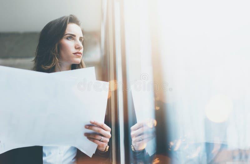 Tragender Anzug der Porträtgeschäftsfrau und halten Papiere in den Händen Dachbodenbüro des offenen Raumes Panoramischer Fensterh lizenzfreie stockbilder