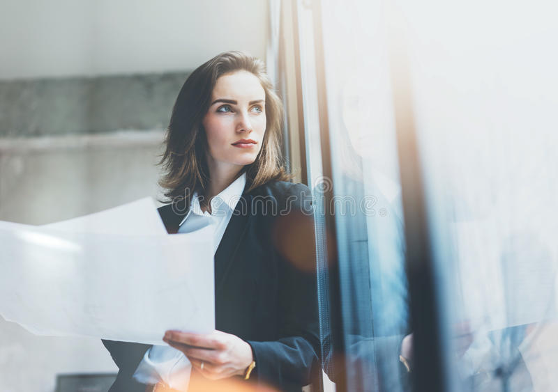 Tragender Anzug der Porträtgeschäftsfrau, Unterhaltungssmartphone und halten Papiere in den Händen Dachbodenbüro des offenen Raum lizenzfreie stockfotos