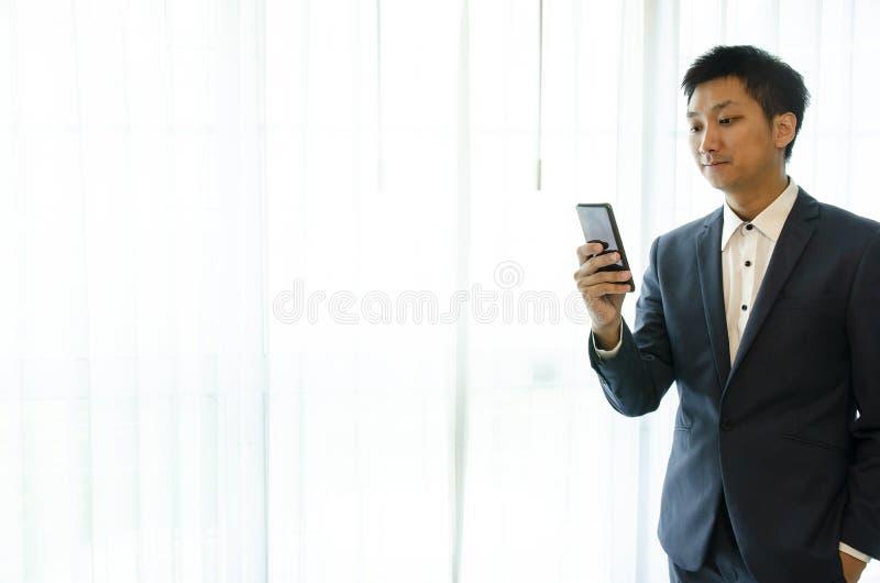Tragender Anzug des Geschäftsmannes, Smartphone schauend Dachbodenb?ro des offenen Raumes Panoramischer Fensterhintergrund stockbild