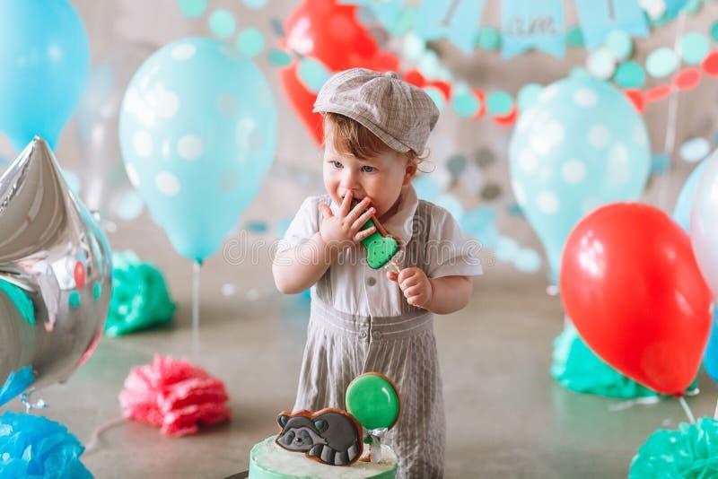 Tragender Anzug und Hut des entzückenden Babys, die einen kleinen Geburtstagskuchen in verziertem Studioraum essen stockfotos