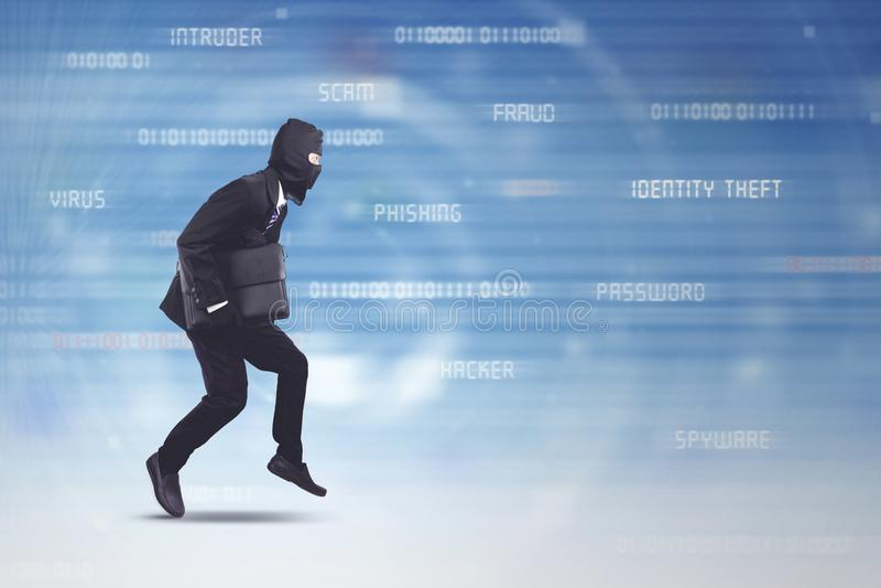 Tragender Anzug und Maske des Diebes, die Laptop stehlend läuft lizenzfreies stockbild