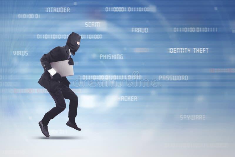 Tragender Anzug und Maske des Diebes, die Laptop stehlend läuft lizenzfreie stockbilder