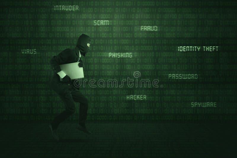 Tragender Anzug und Maske des Diebes, die Laptop stehlend läuft stockfoto