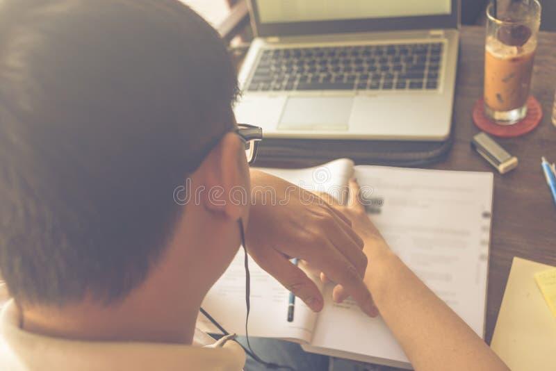 Tragender asiatischer Student der Gläser, der mit Laptop und Arbeitsbuch studiert stockfotografie