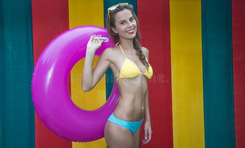 Tragender Bikini der recht jungen Frau, der rosa aufblasbaren Ring auf der bunten Wand hält lizenzfreie stockbilder