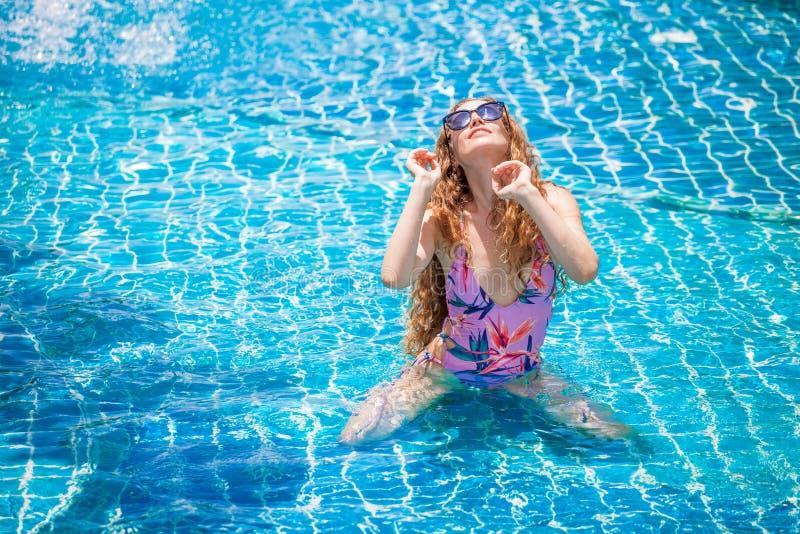 tragender Bikini der schönen jungen sexy Frau mit Sonnenbrille im Swimmingpool Hübsches Mädchen im Badeanzug, der an aufwirft und lizenzfreies stockbild