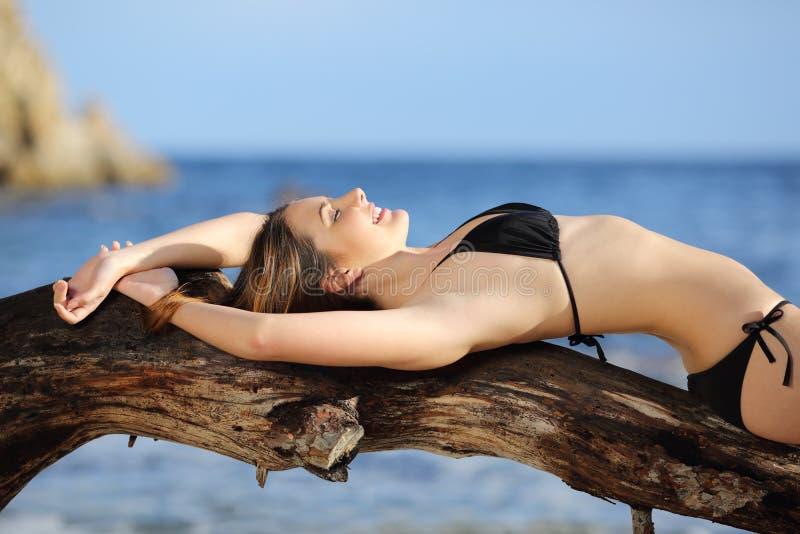 Tragender Bikini der Schönheit, der auf dem Strand ein Sonnenbad nimmt lizenzfreie stockfotos