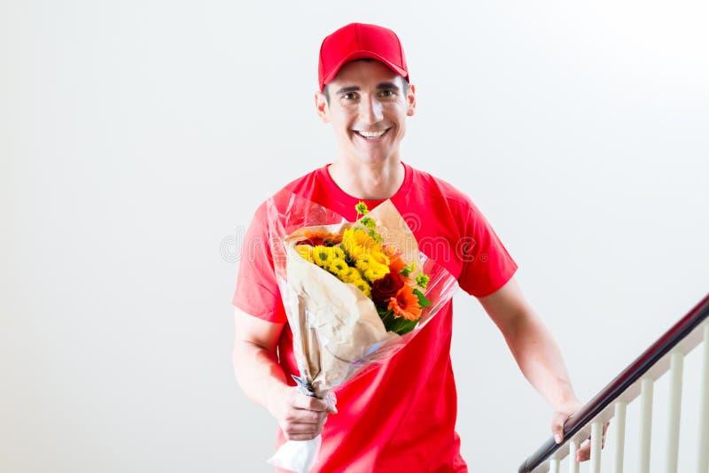 Tragender Blumenblumenstrauß des Lieferers stockbild