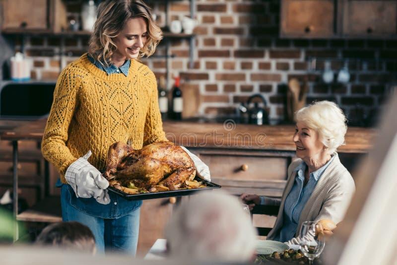 tragender Danksagungstruthahn der Frau für Familienabendessen während ihr älteres Mutterschauen lizenzfreies stockfoto