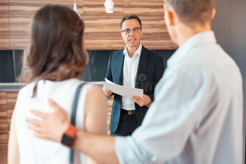 Tragender dunkler Anzug des Grundstücksmaklers, der Papiere beim Sprechen mit Kunden hält lizenzfreies stockfoto