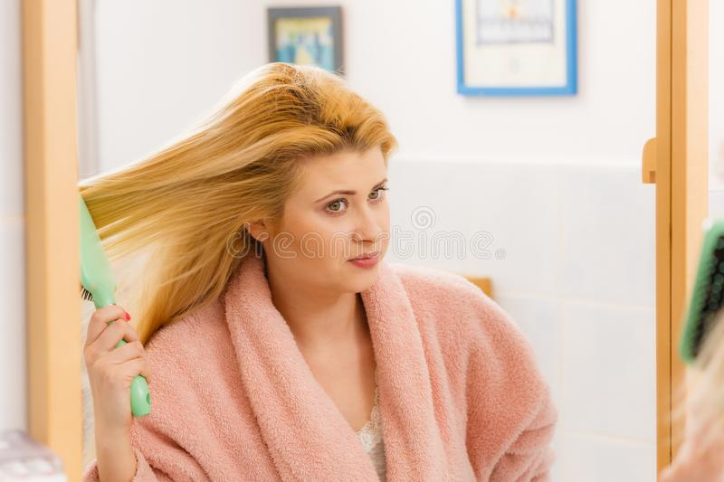 Tragender Hausmantel der Frau, der ihr Haar b?rstet lizenzfreies stockbild