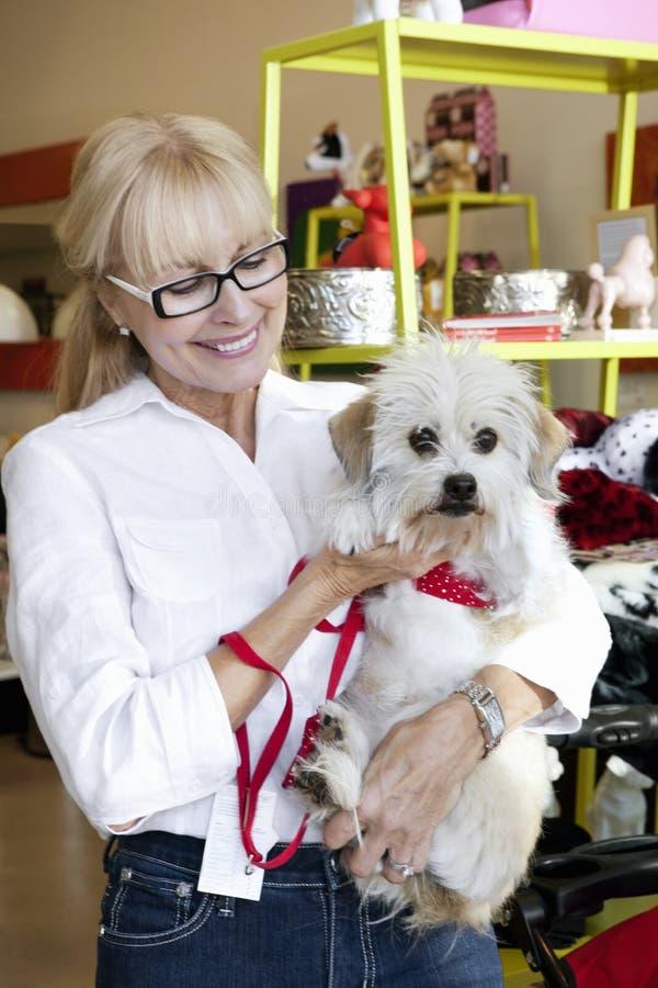 Tragender Hund der glücklichen älteren Frau im Geschäft für Haustiere lizenzfreie stockfotos