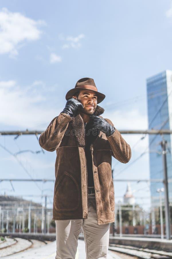 Tragender Hut des attraktiven überzeugten hispanischen Mannes und alte blasse lange Hose Geschäftsmannwartezug auf Plattform stockfotos