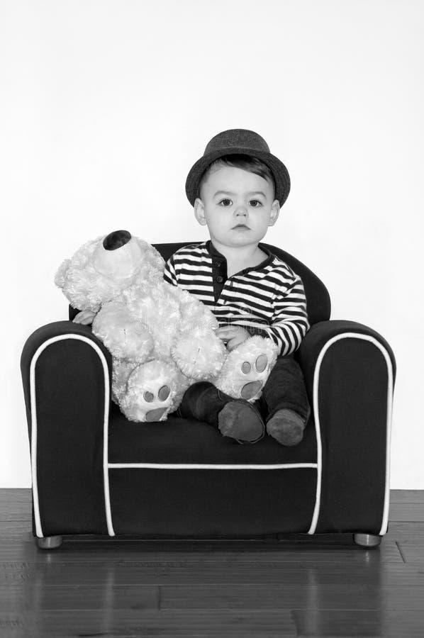 Tragender Hut des Jungen mit Teddybären im Schwarzweißfotografie lizenzfreie stockfotos