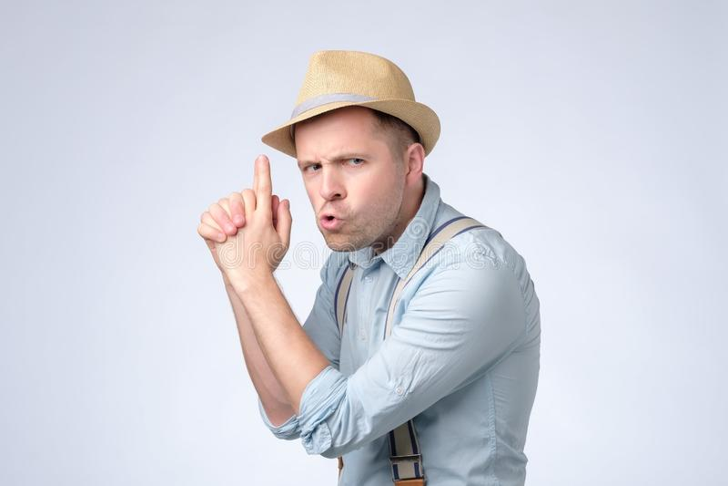Tragender Hut und Hosenträger des jungen gut aussehenden Mannes, die symbolisches Gewehr mit Handzeichen halten lizenzfreie stockfotografie