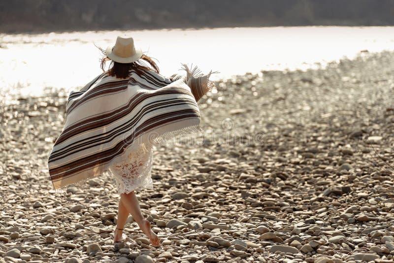 Tragender Hut und Poncho des Schönheitsreisenden, die in Fluss gehen stockfoto