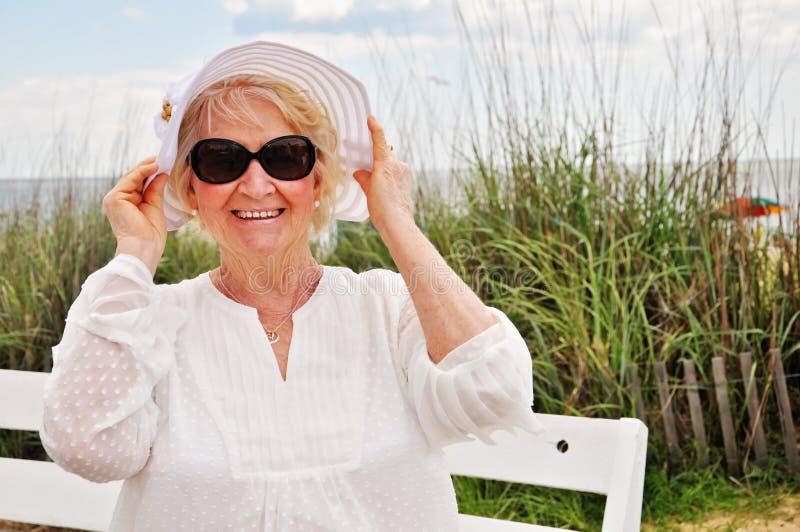 Tragender Hut und Sonnenbrille älterer älterer Dame am Strand lizenzfreie stockbilder