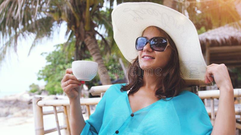 Tragender Hut und Sonnenbrille des eleganten hübschen Lächelnmädchens am Feiertag, sitzend im Strandcafé mit szenischen Ansichten lizenzfreie stockfotos