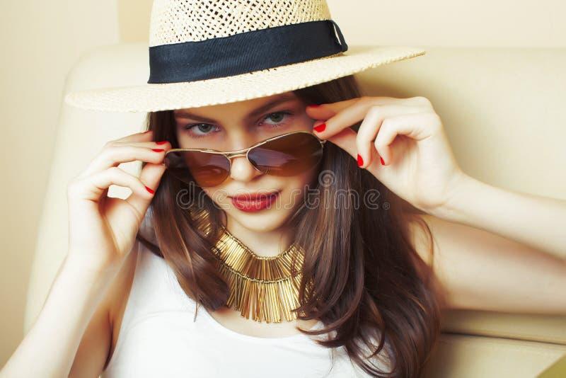 Tragender Hut und Sonnenbrille des jungen h?bschen brunette M?dchens, die allein zu Hause, Lebensstilleutekonzept warten stockfoto