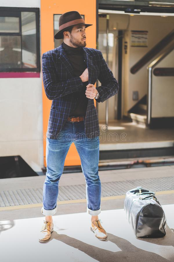 Tragender Hut und Stellung des jungen attraktiven hispanischen Mannes an der Bahnplattform, die auf den Zug wartet vertikal lizenzfreie stockbilder