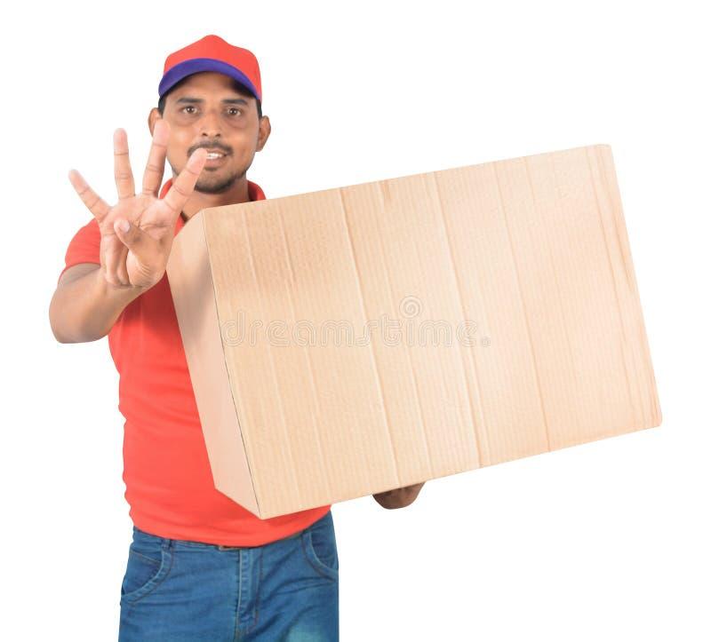 Tragender Karton des glücklichen Lieferers packt vier Finger herein whowing ein lizenzfreies stockfoto