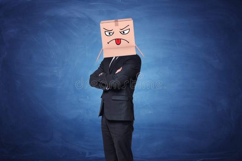 Tragender Kartonkasten des Geschäftsmannes mit dem gemalten verärgerten Gesicht, das Zunge auf ihr zeigt stockfotografie