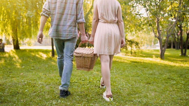Tragender Korb der netten Paare, gehend zum üblichen Platz für Picknick, Freilichtdatum lizenzfreie stockfotos