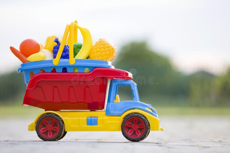 Tragender Korb des hellen bunten Spielzeugauto-PlastiklKWs mit Spielzeugobst und gemüse -draußen am sonnigen Sommertag lizenzfreies stockfoto