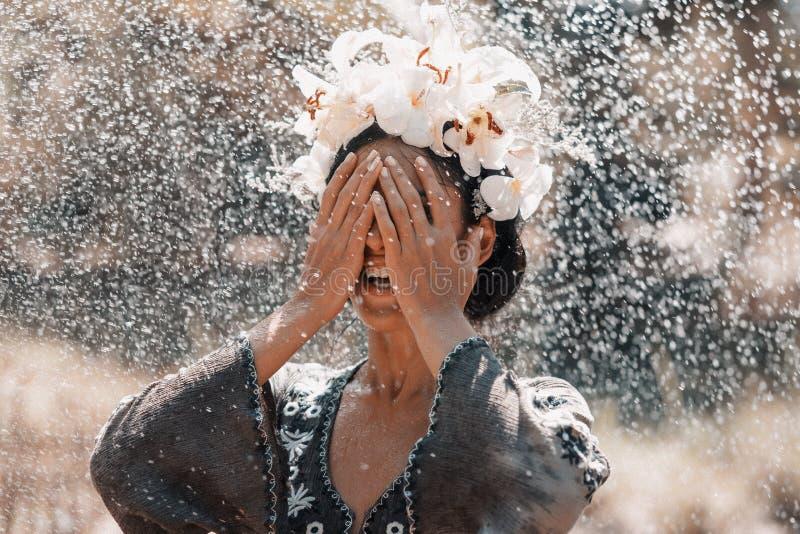 Tragender Kranz der schönen jungen stilvollen Frau unter Sommerregen lizenzfreies stockbild