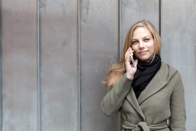 Tragender Mantel der jungen Frau unter Verwendung der Smartphonemetallwand lizenzfreies stockbild