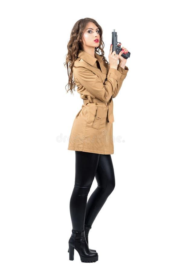 Tragender Mantel des sexy weiblichen Spions, der Seitenansicht der Pistole spannt lizenzfreie stockfotografie