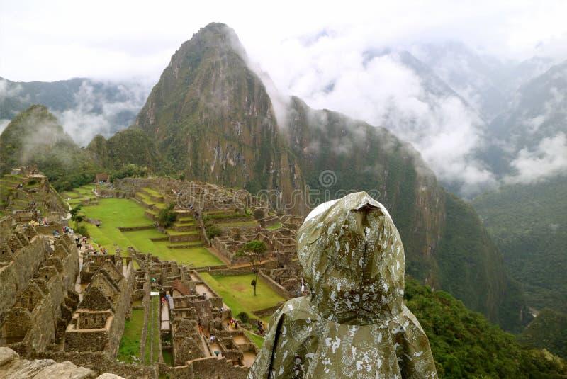 Tragender Regenmantel des weiblichen Besuchers voll von den Regentropfen, welche die Inkazitadelle Machu Picchu im leichten Regen lizenzfreies stockfoto