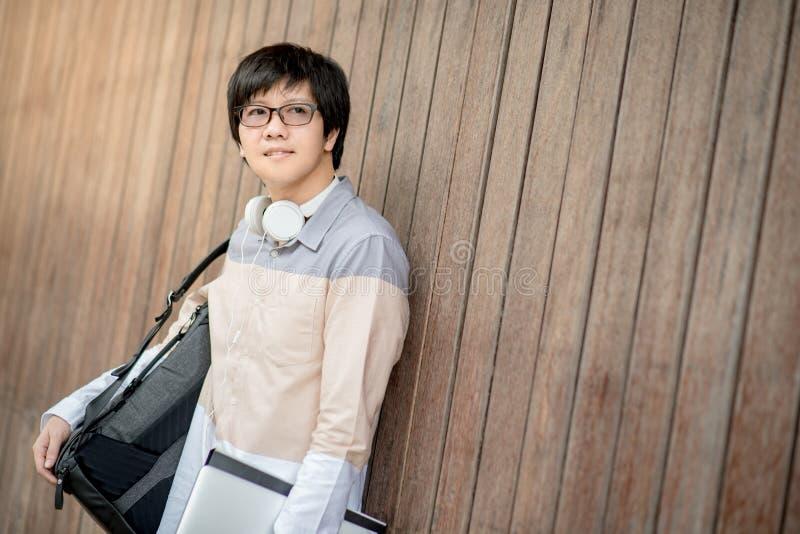 Tragender Rucksack des jungen asiatischen Studentenmannes im College stockfoto