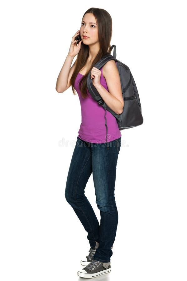Tragender Rucksack des zufälligen jugendlich Mädchens, der am Handy spricht lizenzfreie stockfotos