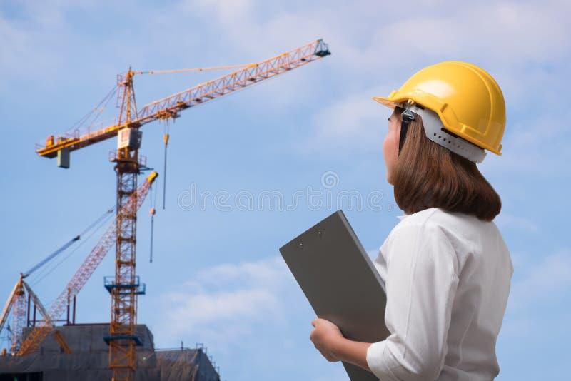 Tragender Schutzhelm des weiblichen Ingenieurs in der Baustelle stockbild