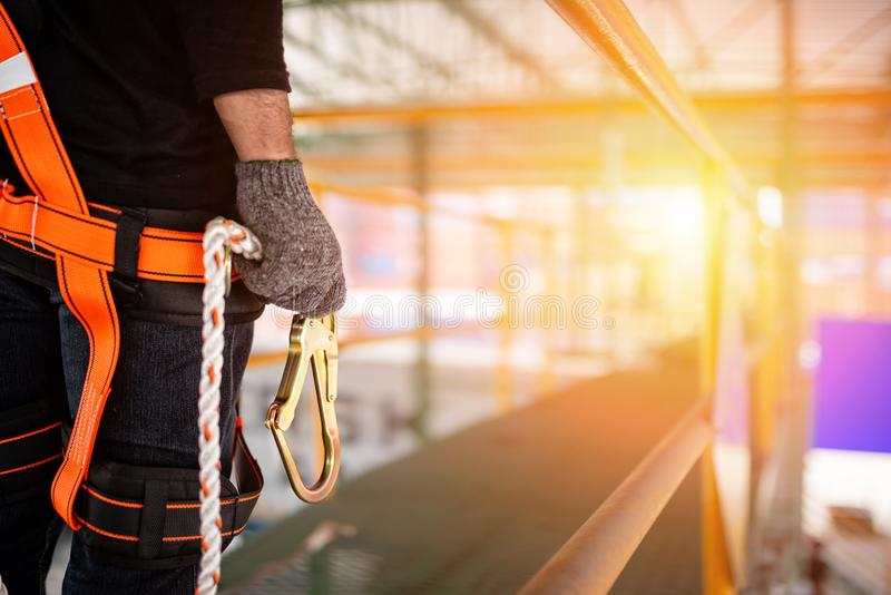 Tragender Sicherheitsgurt des Bauarbeiters und Sicherheitslinie lizenzfreie stockfotografie