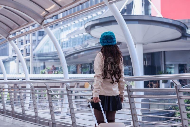 Tragender Strickjackenmantel der asiatischen Reisefrau, blauer Garnhut mit lugg stockfoto