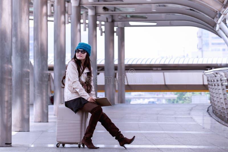 Tragender Strickjackenmantel der asiatischen Reisefrau, blauer Garnhut und Griff stockbild