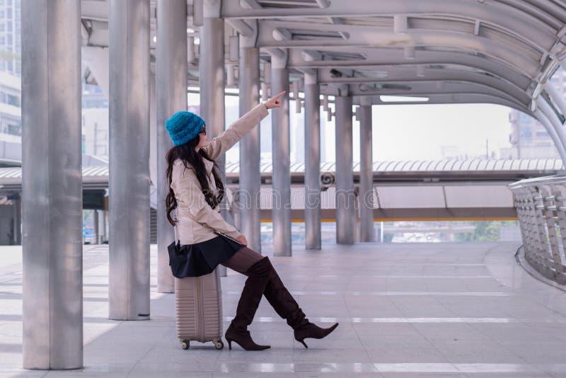 Tragender Strickjackenmantel der asiatischen Reisefrau, blauer Garnhut und Griff stockfotografie