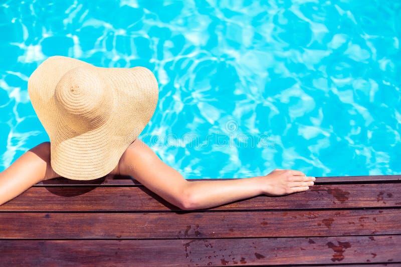 Tragender Strohhut der Frau, der auf hölzerner Plattform durch Poolside sich lehnt lizenzfreies stockfoto