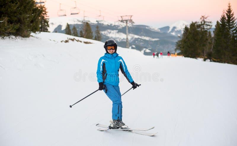 Tragender Sturzhelm der Frau, blaue Sportkleidung, Skischutzbrillen, die mit Skis stehen lizenzfreies stockbild
