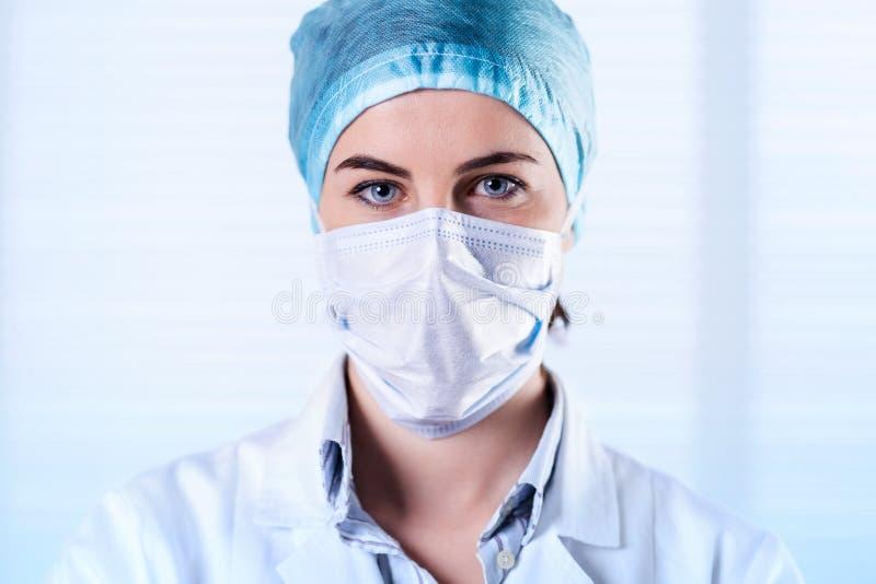 Tragender weißer Mantel, Kappe und Maske des weiblichen Chirurgen stockfoto