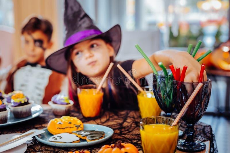 Tragender Zaubererhut des Mädchens für trinkenden Saft und Essen Halloweens von gummiartigen Bonbons lizenzfreies stockbild
