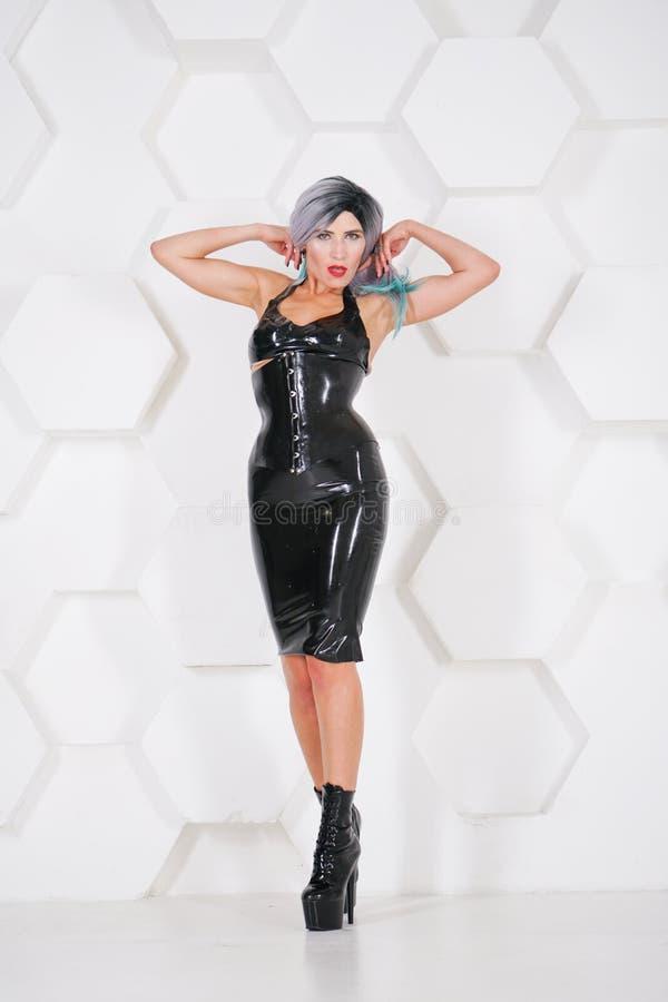 Tragendes alternatives Kostüm des Latex der heißen sexuellen Frau auf futuristischem Hintergrund des weißen Studios lizenzfreie stockfotografie