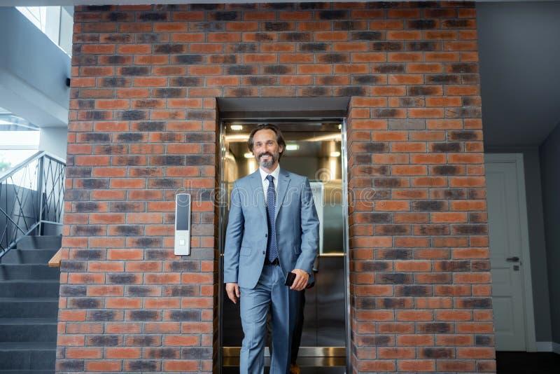 tragendes Anzugs- und Bindungsgefühl des Grau-haarigen Geschäftsmannes motiviert stockfotos