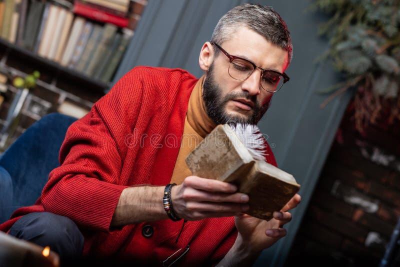 Tragendes Armband des bärtigen reifen Wahrsagers, das wenig altes Magierbuch hält stockbild