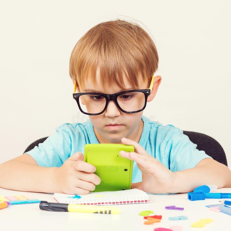 Tragendes Brillenstudieren des Schülers Kleiner Junge tut Hausarbeit Kind unter Verwendung des Taschenrechners, sitzt bei Tisch V stockbilder