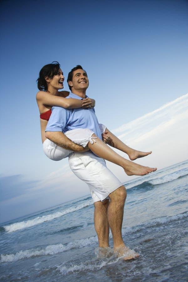 Tragendes Frauendoppelpol des Mannes am Strand. lizenzfreie stockbilder