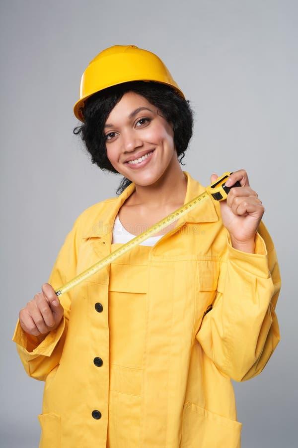 Tragendes Gelb des Frauenerbauers schützen den Sturzhelm und Gesamtes, die Maßband halten lizenzfreie stockfotografie