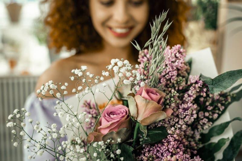 Tragendes gestreiftes einheitliches Gefühl des gelockten Floristen zufriedengestellt mit Ergebnis stockfoto